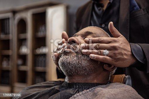 istock Handsome black man in a luxury barber shop 1255879144