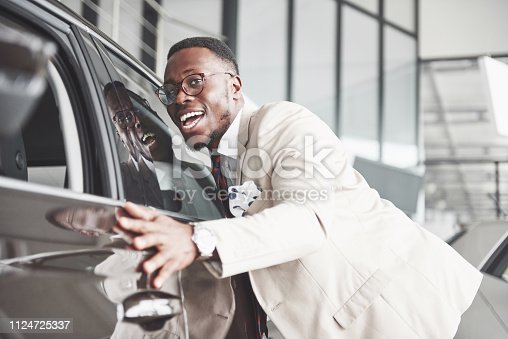 1138561232 istock photo Handsome black man in dealership is hugging his new car and smiling 1124725337