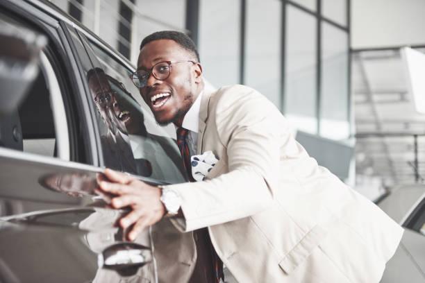 Schöner schwarzer Mann im Autohaus ist sein neue Auto umarmt und lächelnd – Foto