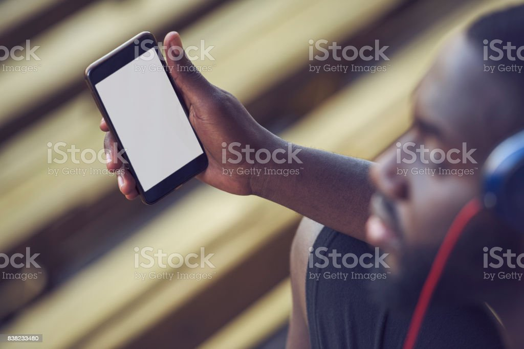 A handsome black man is holding a mock up phone screen, over shoulder view stock photo