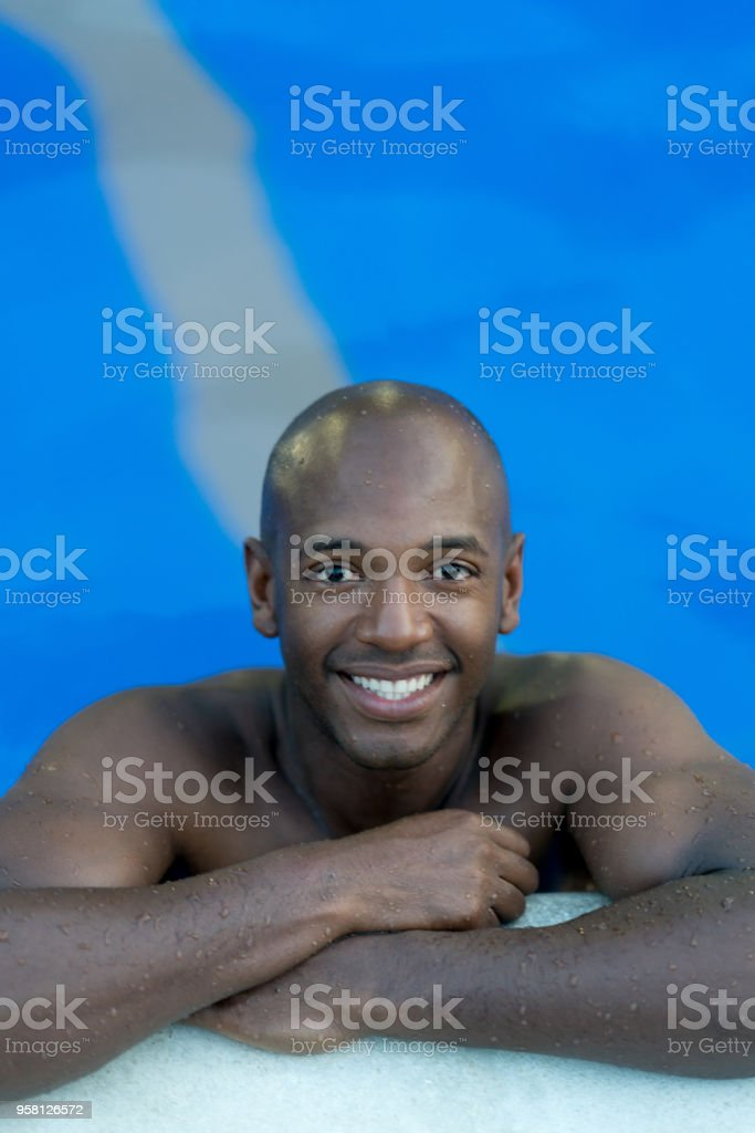 Handsome black man leaning his arms at the edge of the pool looking...