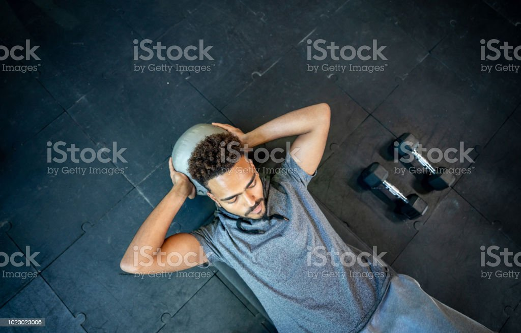 Handsome black man lying on floor working out with a med ball his abs stock photo