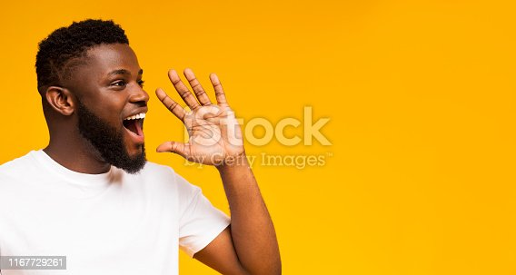 istock Handsome black man shouting at copy space, making announcement 1167729261