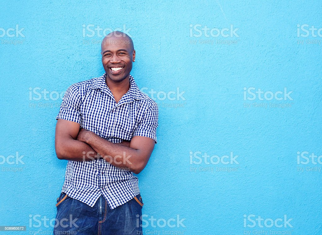 Handsome black man smiling with arms crossed stock photo