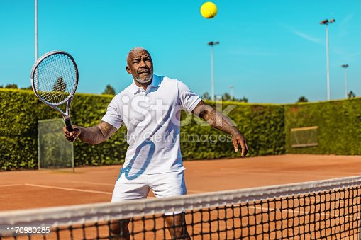 A handsome black middle aged male tennis player on the court on a beautiful summer day in the sun