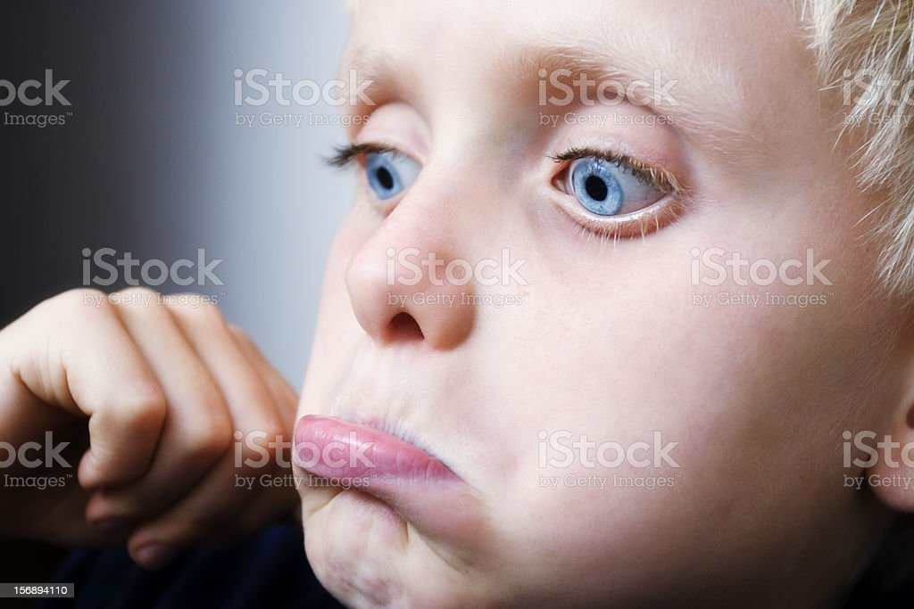 Handsome blond boy looks down and pouts royalty-free stock photo