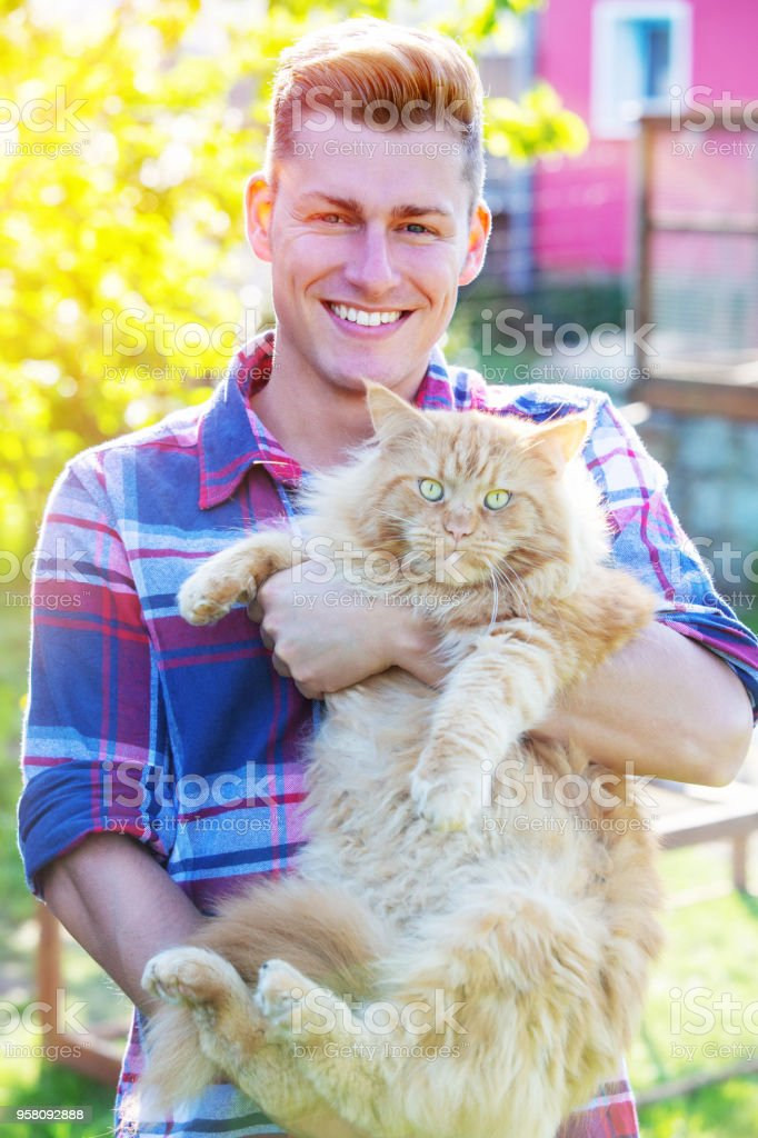 handsome blond man holding a red tabby cat royalty-free stock photo