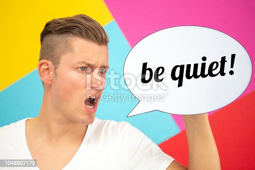 handsome blond man screaming and holding a speech bubble with the words Be Quiet