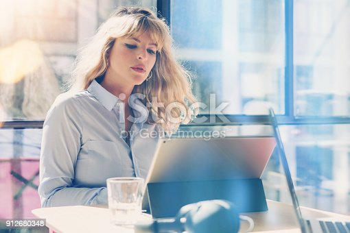 istock Handsome blonde businesswoman working at the modern office loft.Coworker using electronic touch tablet computer on sunny workplace.Horizontal. Blurred background. 912680348