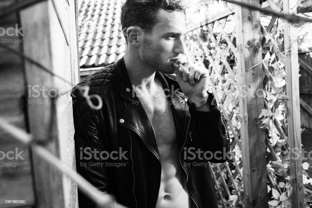 Handsome blonde man with open leather jacket revealing sixpack abs smoking cigarette and looking away from camera stock photo