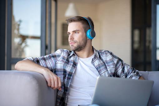 Handsome blue-eyed freelancer feeling good working at home