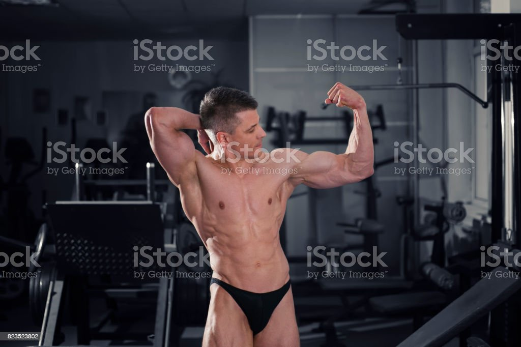 Handsome bodybuilder posing in gym, perfect muscular male body stock photo