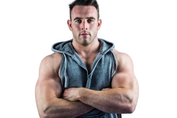 guapo fisicoculturista con los brazos cruzados - hombres grandes musculosos fotografías e imágenes de stock