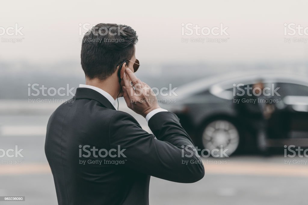 handsome bodyguard standing and listening message with security earpiece on helipad stock photo