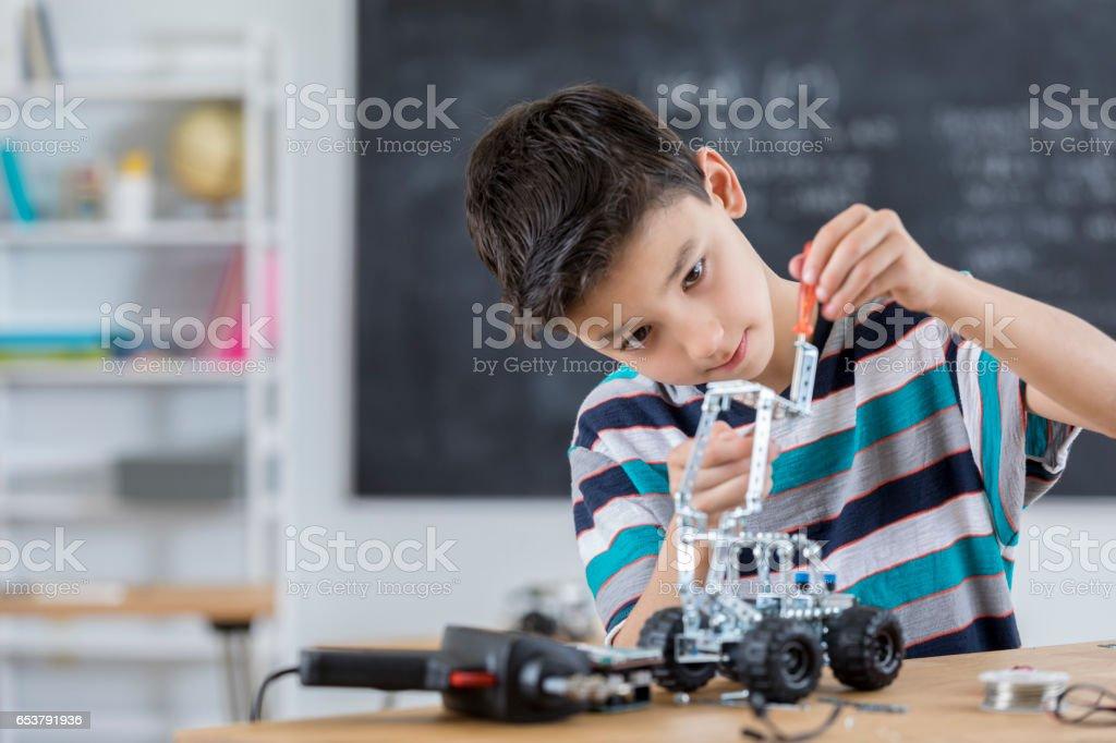 Handsome boy builds robot at school stock photo