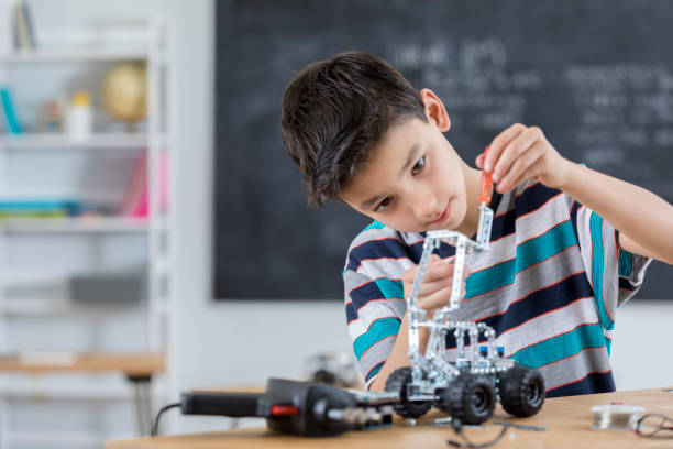 Handsome boy builds robot at school stock photo