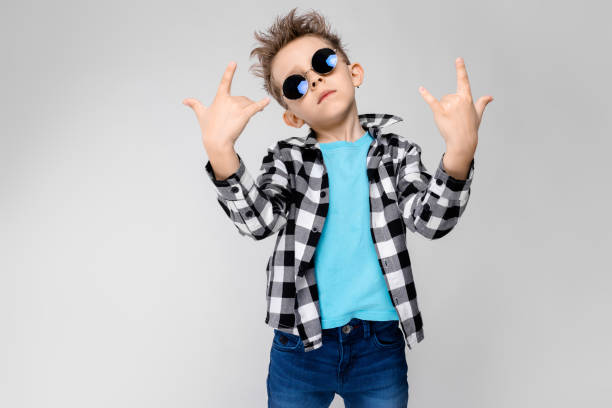 a handsome boy in a plaid shirt, blue shirt and jeans stands on a gray background. the boy is wearing round glasses. redhead boy shows a rocker goat - rock musician stock pictures, royalty-free photos & images