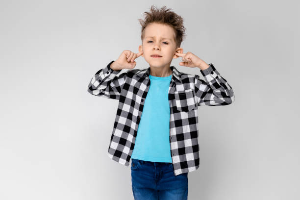 A handsome boy in a plaid shirt, blue shirt and jeans stands on a gray background. The boy folded his arms over his chest. The boy covered his ears with his fingers Charming happy child on gray background. The boy's hair is up. The boy has a hairstyle. The boy stuck his fingers in his ears protruding stock pictures, royalty-free photos & images