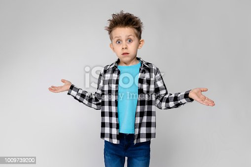 Charming happy child on gray background. The boy's hair is up. The boy has a hairstyle. The boy spread his hands in both directions