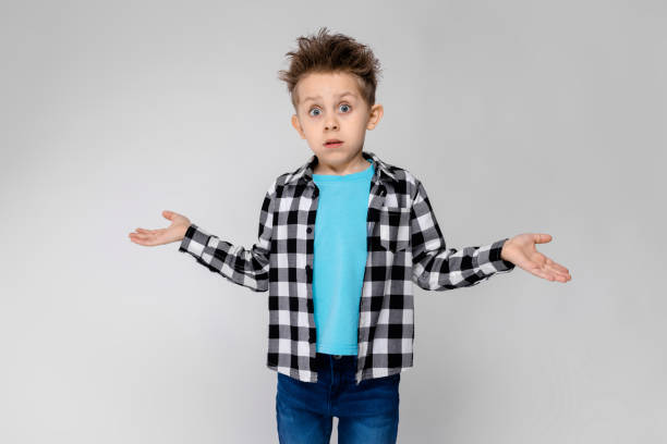 A handsome boy in a plaid shirt, blue shirt and jeans stands on a gray background. The boy spread his hands in both directions stock photo