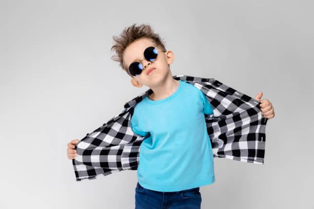 ein hübscher junge in ein kariertes hemd, blaues hemd und jeans steht auf einem grauen hintergrund. der junge ist eine runde brille. der junge lächelt und zieht sein hemd weg - gedehnte ohren stock-fotos und bilder