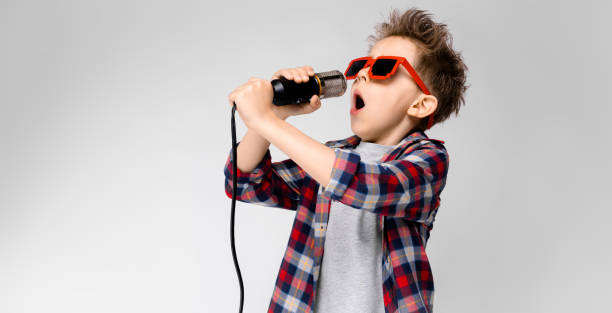 A handsome boy in a plaid shirt, gray shirt and jeans stands on a gray background. A boy wearing sunglasses. Red-haired boy sings into the microphone Charming happy child on gray background. The boy's hair is up. The boy has a hairstyle. The boy in round sunglasses. A handsome boy with a red hair color. The boy sings into the microphone. singing stock pictures, royalty-free photos & images
