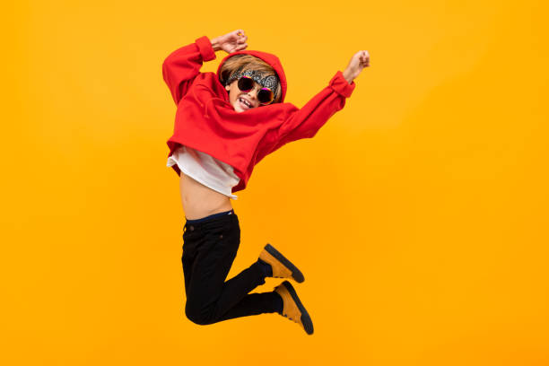 handsome boy with a bandana on his head in a red hoodie with glasses jumps on an isolated orange background stock photo