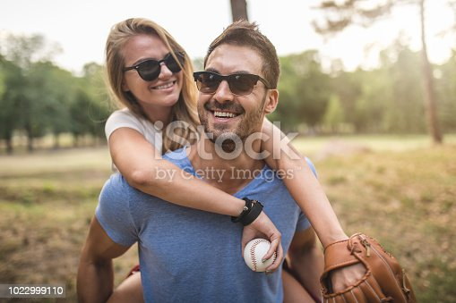 istock Handsome boyfriend carrying his girlfriend on his back in a park 1022999110