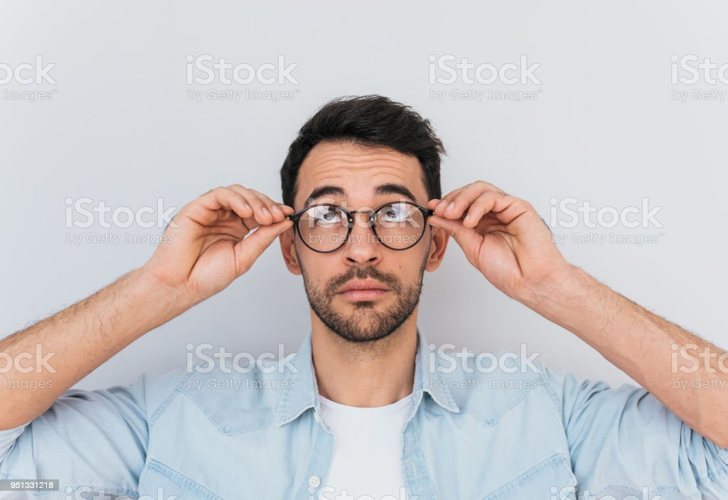 ce32acf556c9 Handsome breaded young man looks up, wears round trendy spectacles, wear  blue shirt. Stylish Caucasian male looks at advertisment, copy space for  text ...