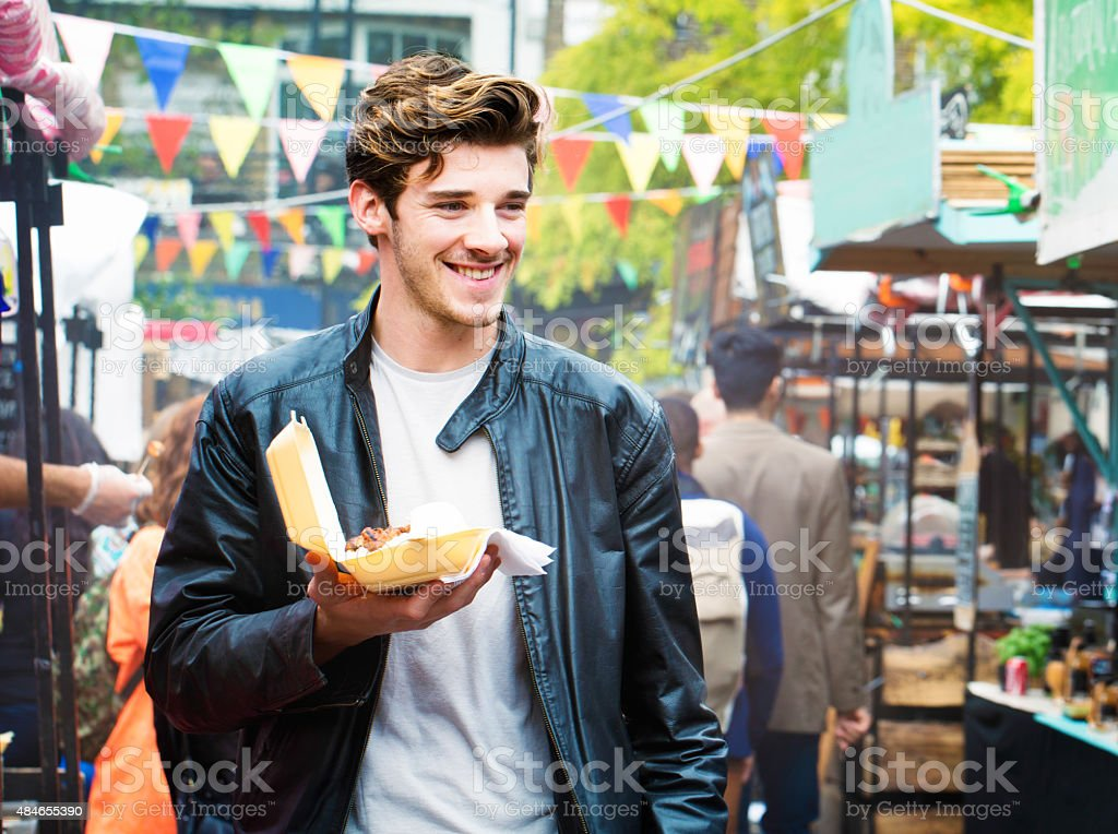 Handsome British man walks through fair market with street food stock photo