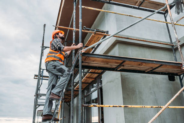 handsome builder climbing on scaffolding at construction site handsome builder climbing on scaffolding at construction site scaffolding stock pictures, royalty-free photos & images