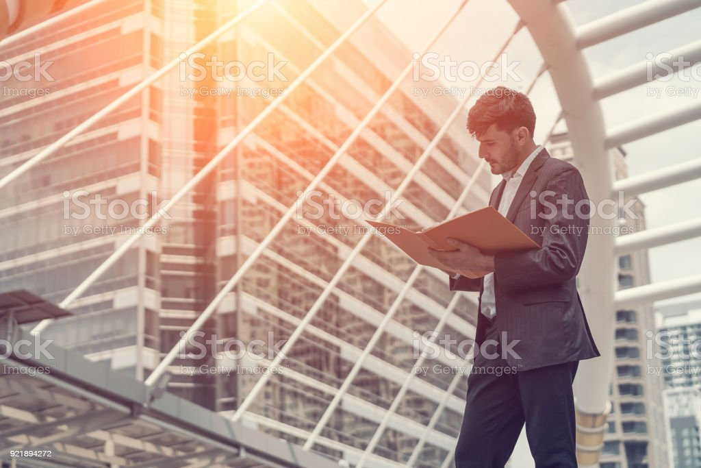 Handsome business man holding document. Concept of business work thinking. stock photo