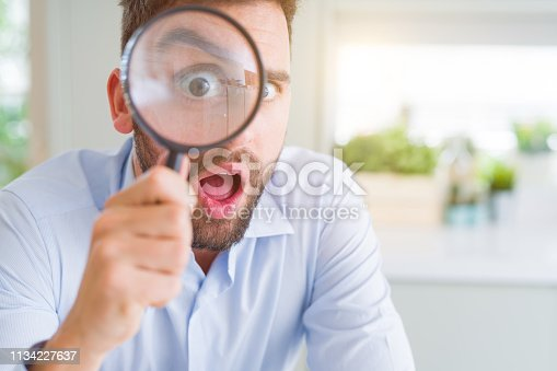 istock Handsome business man holding magnifying glass close to face, big eyes and funny expression 1134227637