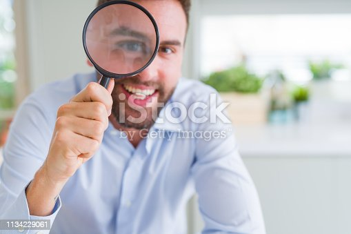istock Handsome business man holding magnifying glass close to face, big eyes and funny expression 1134229061