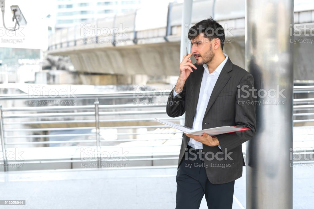 Handsome business man holding pen and document. Concept of business work thinking. stock photo