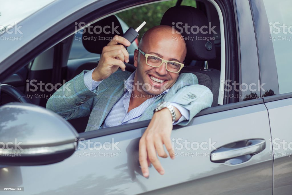 Handsome business man male holding car keys in hand showing his new car stock photo