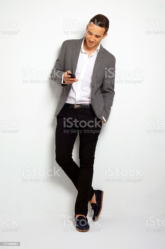 Handsome business man reading an SMS on smartphone. stock photo