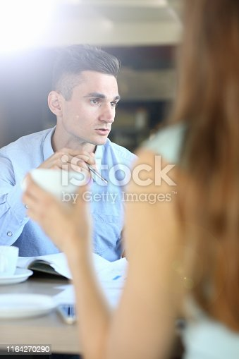 Selective focus on confident male sitting in cafe. Corporate boy explaining something to group of company people. Model holding ball pen and looking at workers. Blurred background
