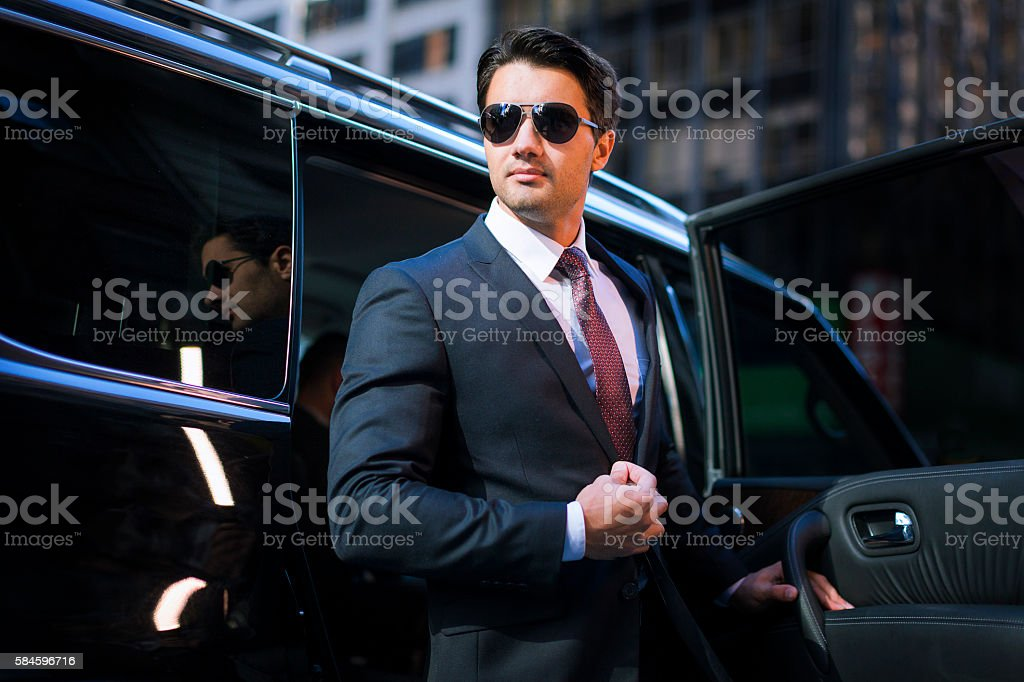 Handsome businessman arriving in executive car stock photo