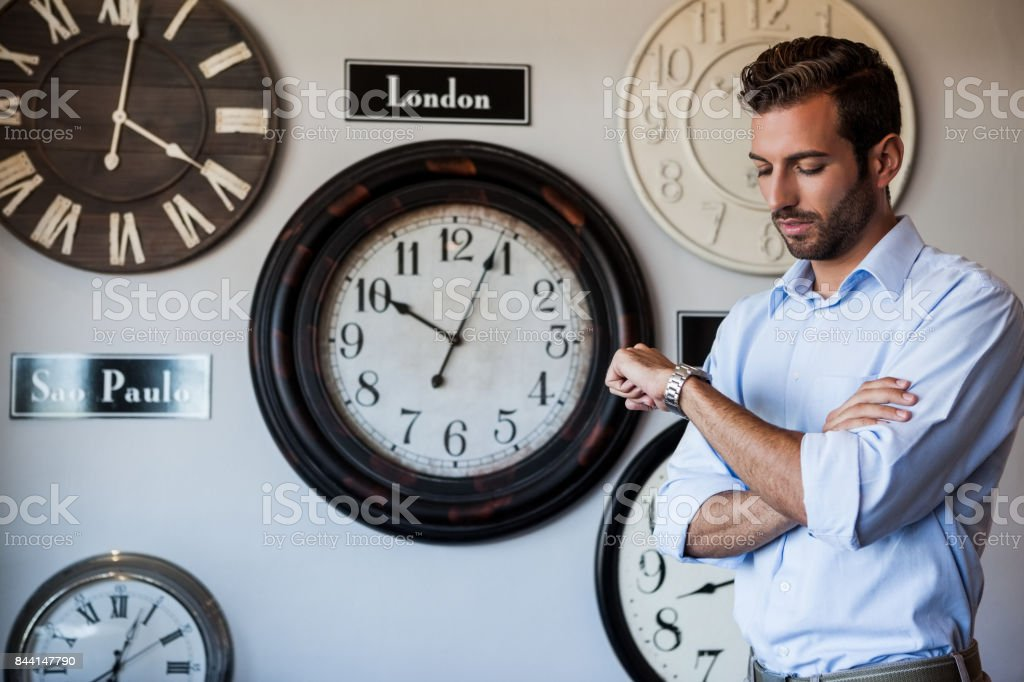 Handsome businessman checking the time stock photo