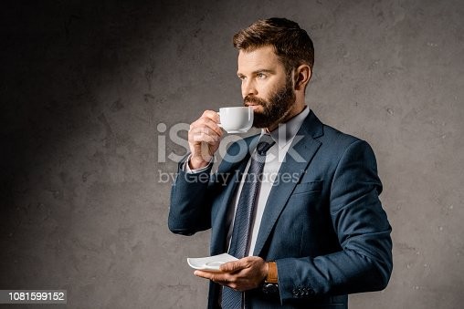 1081599130 istock photo handsome businessman drinking coffee and holding saucer 1081599152