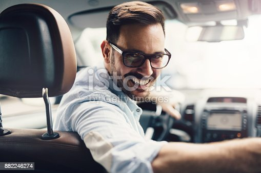 istock Handsome businessman driving a car 882246274