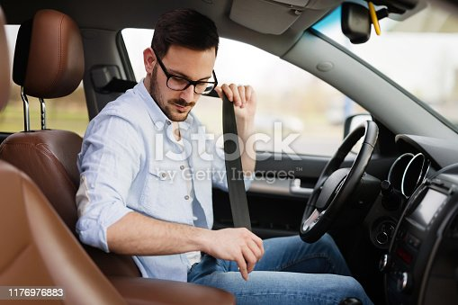 849721378istockphoto Handsome businessman driving a car to work 1176976883