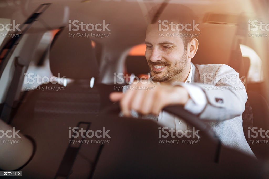 Handsome businessman driving car stock photo