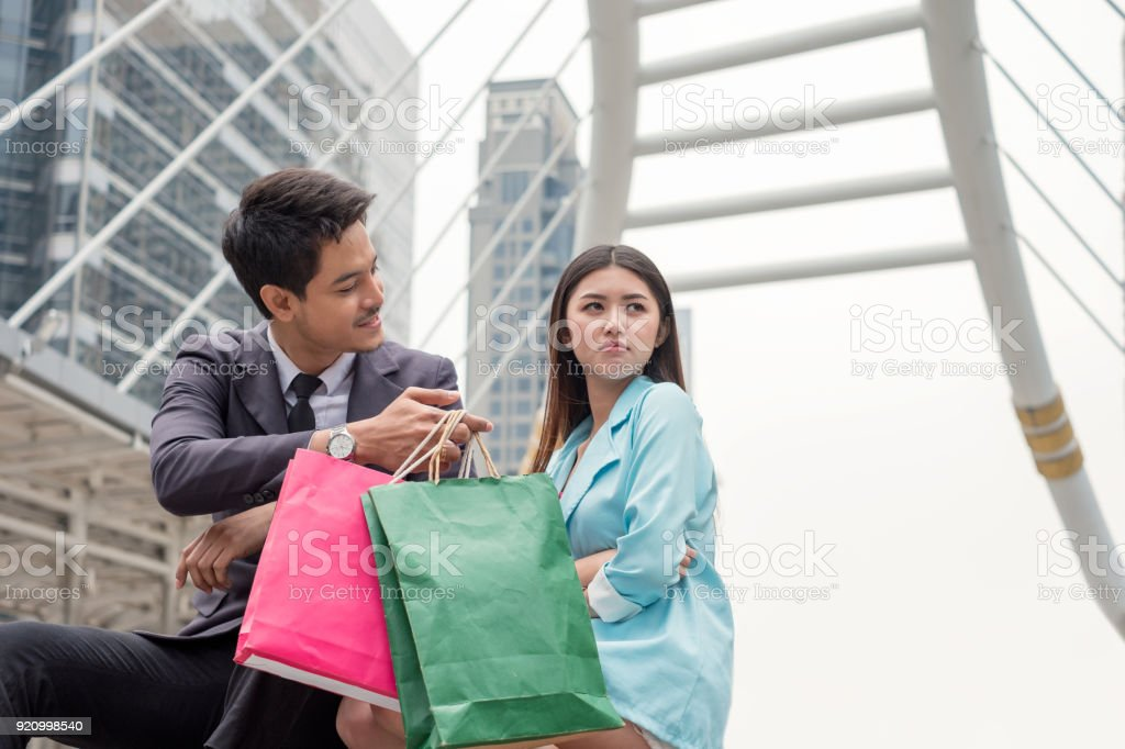Handsome businessman give paper bag for reconcile with beauty asian woman touchy sulking stock photo