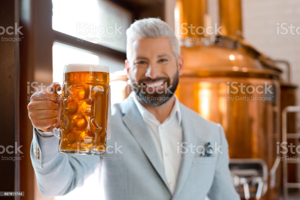 Handsome businessman holding a beer mug at brewery Handsome businessman holding a beer mug at brewery. Brewery owner with a glass of fresh beer. Adult Stock Photo
