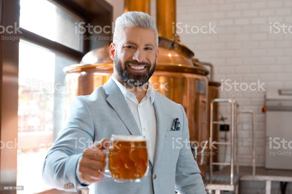 Handsome businessman holding a beer mug in microbrewery Portrait of handsome businessman holding a beer mug in microbrewery. Brewery owner with a glass of fresh beer. Adult Stock Photo