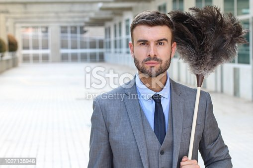 istock Handsome businessman holding a feather duster 1027138946