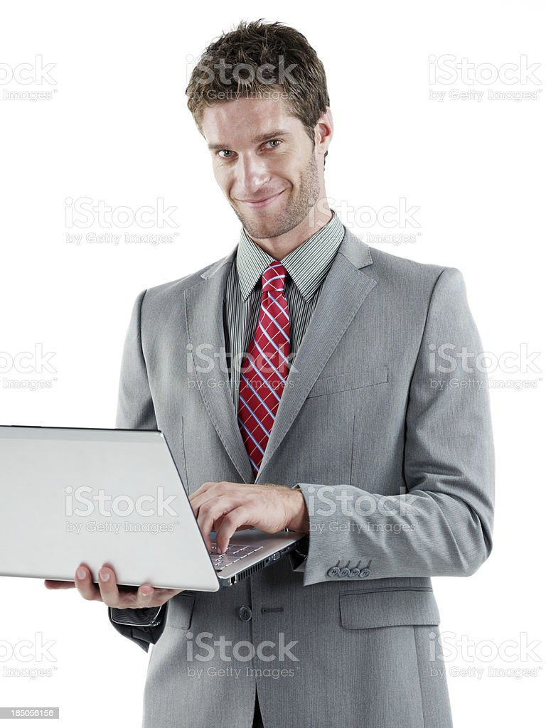 Handsome businessman holding a laptop smiling royalty-free stock photo