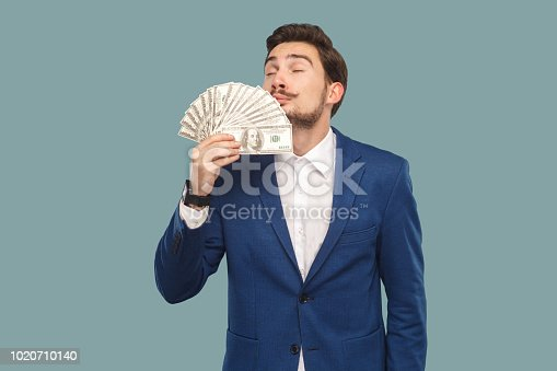istock Handsome businessman in blue jacket standing and holding many dollars in hand and smelling and feeling smell of richness with closed eyes. 1020710140